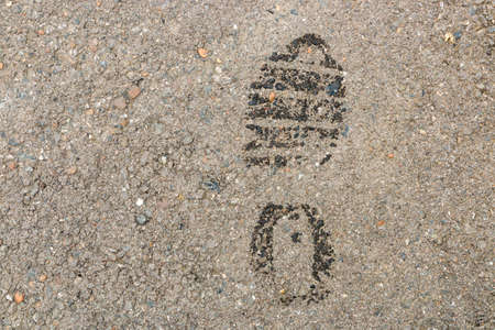 Wet footprint on asphalt surface. warning - thief.