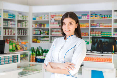 smart and confident woman pharmacist holding her arms crossed and smiling Banque d'images