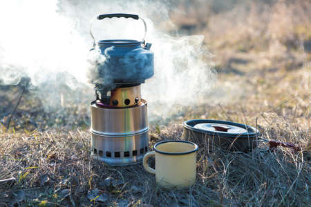 outdoor tea preparation. boiling water in kettle on portable wood burner with smoke