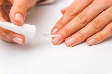 closeup beautiful female hands painting nails with transparent polish Standard-Bild