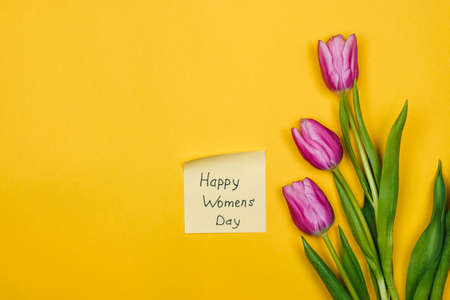 beauty of march. purple tulips and sticky note over yellow background. happy womens day