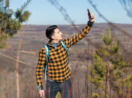 young man in casual clothes lost into the wild trying to catch signal on the phone