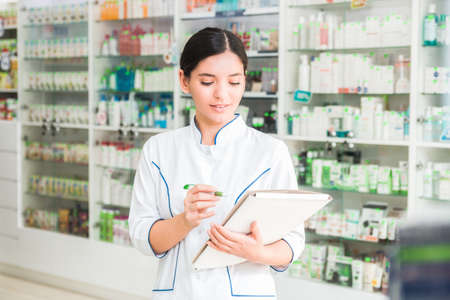 smart and confident woman pharmacist holding a folder and making notes