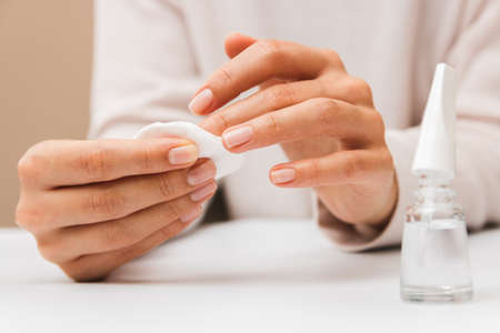 closeup woman hands removing paint from nails with cotton pad Imagens