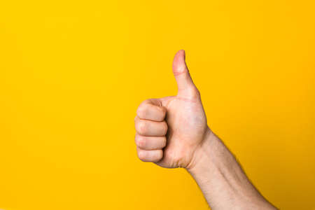 male big thumb up against yellow background with copy space. hand with like sign.