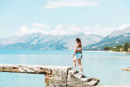 travel adventure begins. young beautiful woman walking along the ocean and looking to the mountains.