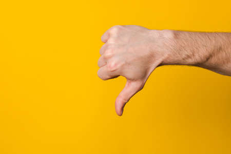Image of human hand showing thumb down in isolation