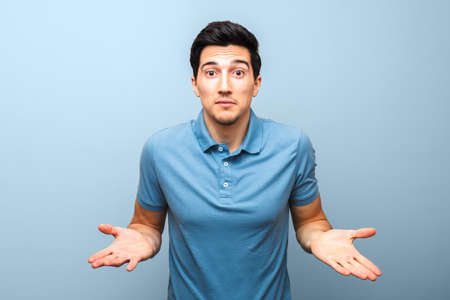 handsome brunette man in blue polo shirt with serious face gesturing with his hands against a blue background. studio shoot. there is nothing to do. Standard-Bild - 143296721