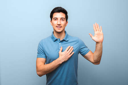 handsome young man with neutral smile in blue polo shirt with hand on chest giving oath against blue background. studio shoot.