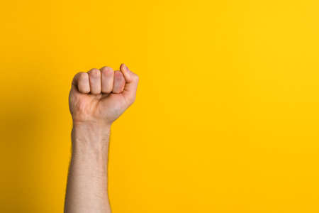 close up man hand fist over a yellow background. winner and power sign.