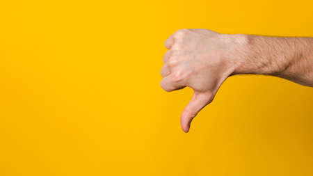 not good and not approved. close up hand of a man showing thumb down dislike sign over yellow background with copyspace for design