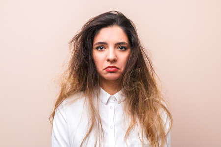 sad woman with tangled hairs in white shirt against pink background. morning womans routine