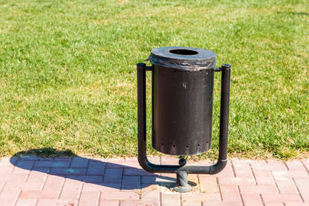 black trash can on walking path by green lawn in park in spring.