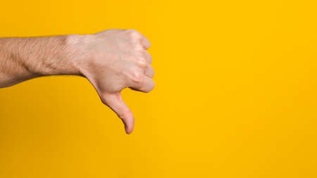 not good and not approved. close up hand of a man showing thumb down dislike sign over yellow background with copyspace for design.