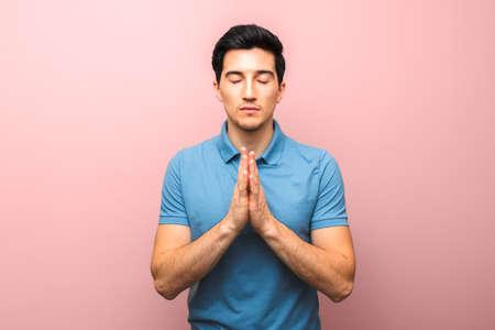 prier pour l'amérique. homme en chemise bleue priant pour le monde avalé par la pandémie de coronavirus sur fond rose rouge Banque d'images