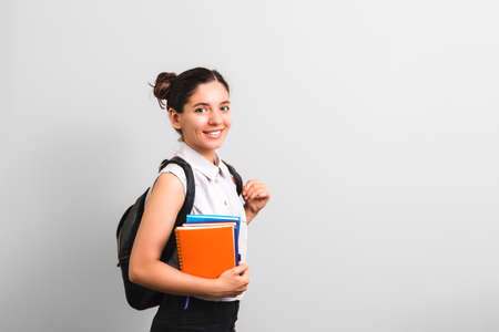 attractive female student with dimples in cheeks smiling holding notebooks in one hand and backpack on shoulders with cute face expression Foto de archivo