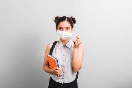 beautiful female student removing or putting on protective mask on her face holding notebooks in one hand and backpack on shoulders with cute face expression.