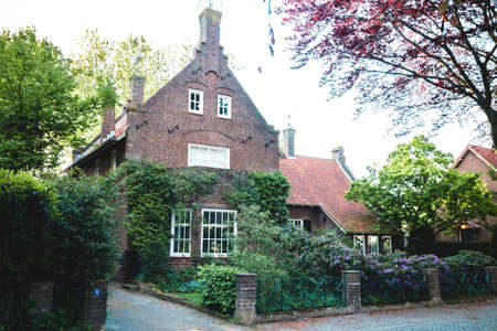 beautiful detached old brick house with garden in front of it in the Netherlands. Dutch real estate home. Foto de archivo