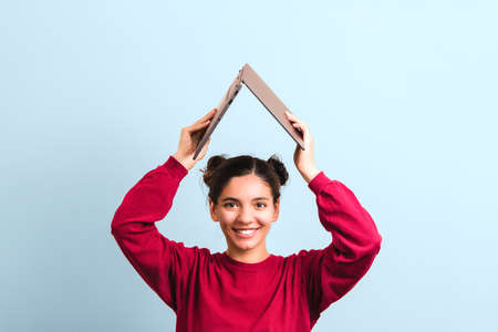 young joyful woman student with beautiful smile holding an opened laptop over her head in form of roof. investing in education. Foto de archivo