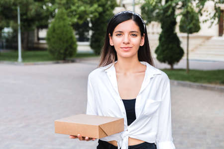 attractive caucasian woman in white shirt and with head bezel holding carton box in palm outdoor in city park. takeaway food or delivery concept. Foto de archivo