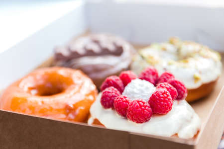 four pieces of totally different colorful and delicious looking donuts in ecological carton box. appetising fast food dessert.