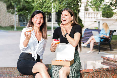 lifestyle portrait of two attractive caucasian girls laughing enjoying delicious looking donuts outdoor in city park. junk but tasty food for positive feeling Foto de archivo