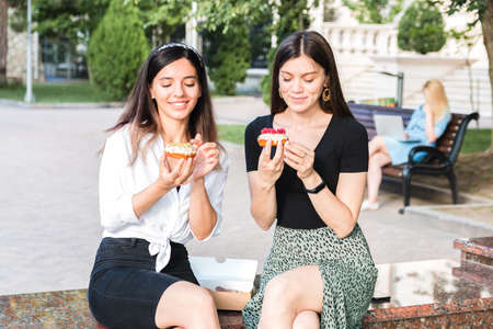 lifestyle portrait of two attractive caucasian girls enjoying delicious looking donuts outdoor in city park. junk but tasty food for positive feeling. Foto de archivo
