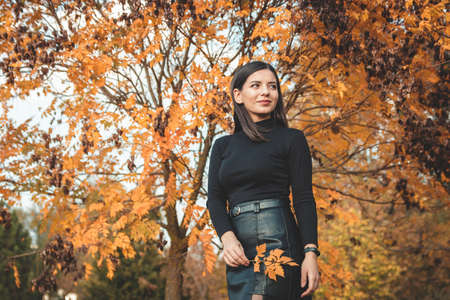 fall scene beautiful autumn portrait of attractive young woman in park against tree with yellow orange leaves holding a tender twig and looking away in the distance.