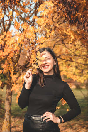 fall scene beautiful autumn portrait of attractive young woman in park against tree with yellow orange leaves holding a tender twig over her eye and looking directly into the camera. Foto de archivo