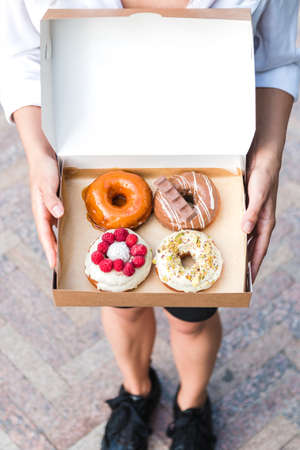 close up hands holding four pieces of totally different colorful and delicious looking donuts in ecological carton box. appetising fast food dessert.