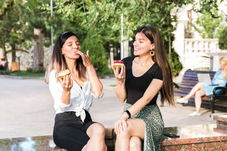 lifestyle portrait of two attractive caucasian girls laughing enjoying delicious looking donuts outdoor in city park. junk but tasty food for positive thinking.