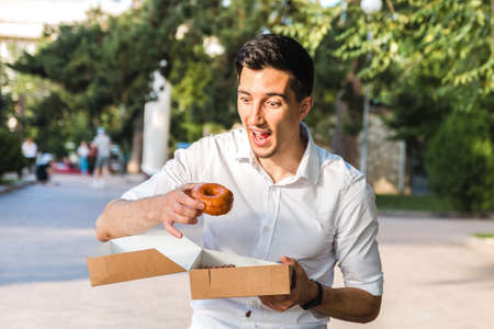 handsome caucasian young man in white shirt enjoying delicious caramel donut in city park. junk but tasty food for positive mood. Foto de archivo