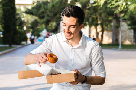 handsome caucasian young man in white shirt enjoying delicious caramel donut in city park. junk but tasty food for positive thinking.