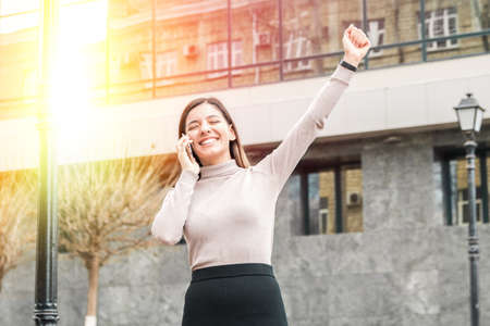 success achieved young attractive business woman or student in front of a modern building business centre or university campus speaking on phone good news or approvement scene. Foto de archivo
