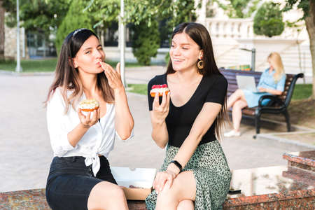 portrait of two beautiful girls friends enjoying delicious donuts with caramel and raspberry in city park. junk but tasty food for positive mood.