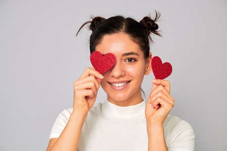 sharing love and valentines. attractive young woman brunette in white casual fashion t-shirt holding two sparkling hearts over her eyes giving beautiful smile Foto de archivo
