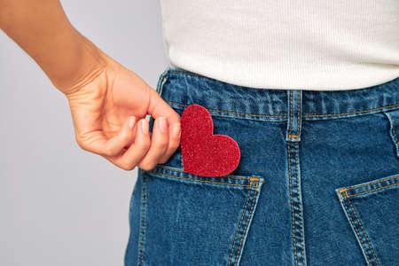 woman holding a small sparkling red heart putting it in or taking off the pocket of her jeans. Sharing and receiving Valentines, keeping love on you