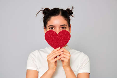 young attractive cheerful ethnicity woman in love holding a big red sparkling heart valentine and covering her mouth and nose while smiling with her eyes