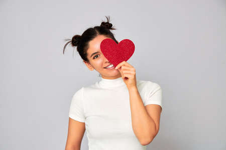 cheerful woman in love with funny hairstyle holding a small red sparkling heart valentine and covering one eye while smiling