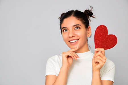 choosing the right variant. portrait of woman holding a sparkling red heart valentine thinking while smiling Foto de archivo