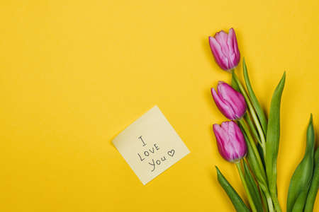 Pink, purple tulips and a sticky note saying I love you on yellow background Foto de archivo