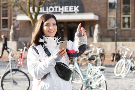 Escape in a city. Young ethnicity woman in early spring using a phone for guiding herself on streets
