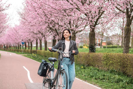 beautiful young woman of mixed races minority riding on bicycle in bloomy spring in casual clothes with attractive smile. lifestyle recreational portrait Foto de archivo
