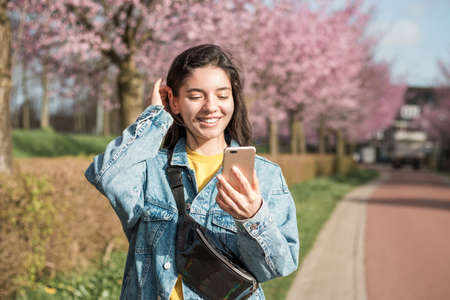 cheerful mixed races woman using phone on the street for a video call or order online Foto de archivo