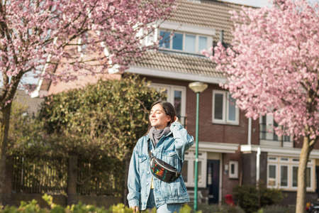 young cheerful mixed races woman outdoor in front of her house taking some fresh air under sunbeams after quarantine