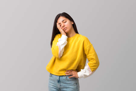 tired young attractive multi ethnicity woman in trendy yellow sweater against light grey background with palm on her face Foto de archivo