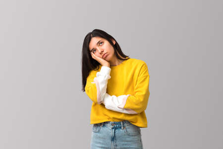 tired young attractive multi ethnicity woman in trendy yellow sweater against light grey background with palm on her face looking up