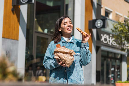 attractive girl eating with big pleasure tasty food from take away cafe in the street. you deserve it