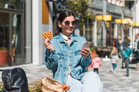 cheerful young woman enjoying tasty waffles in front of a cafe in the street. take away food in the city Foto de archivo