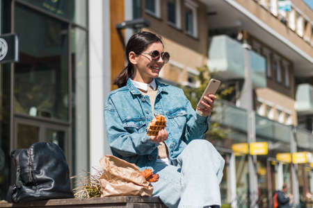 attractive girl eating in the street in the city while using phone to rate the takeaway food company for delicious menu